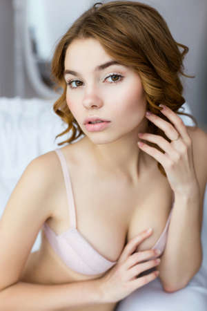 sensually: Portrait of young beautiful attractive lady wearing pink lingerie and sensually looking at camera