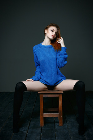 elegancy: Young beautiful woman posing in blue knitted sweater sitting on chair