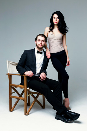 Handsome man in suit and pretty brunette female model on grey background