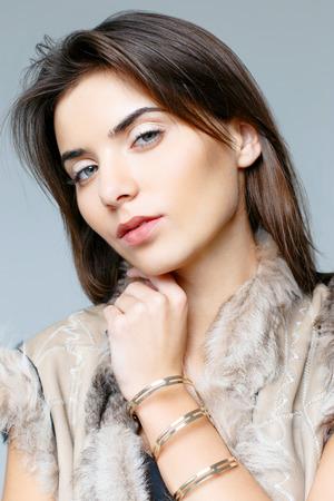 denim shorts: Fashionable beautiful woman in a fur vest and denim shorts