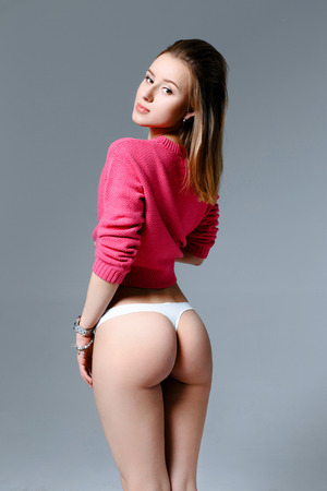 sexy sweater: Sexy woman with perfect body in a pink sweater and underwear posing in studio Stock Photo