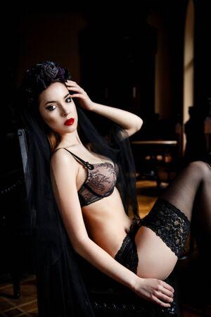cabeza de mujer: Mujer hermosa en medias y ropa interior con una corona en la cabeza. Hembra de la belleza. piel perfecta y maquillaje. labios rojos
