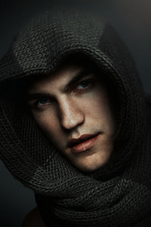 Fashion man portrait wearing knitted scarf on had on dark background