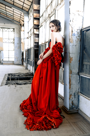 ancient sexy: Beautiful, brunette woman in an old, abandoned house, wearing a red dress, Stock Photo