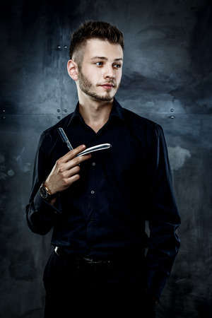 straight razor: Elegant young handsome man. Studio fashion portrait.Portrait of a young brutal man with straight razor