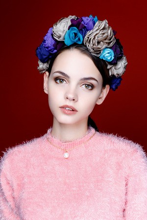 turnanzug: Beautiful model with a wreath of flowers on her head on red background