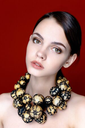 furs: Portrait of pretty young woman with beads on red background Stock Photo