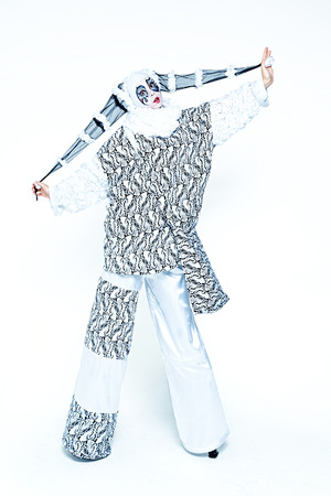 One cheerful female clown dressed in black and white cloth on a white background Stock Photo