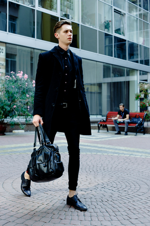 handsome young man in black coat outdoors on building background Stock Photo