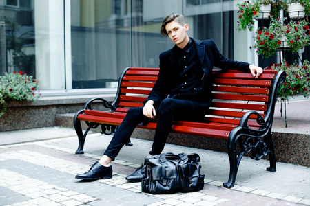 handsome young man in the autumn park sitting on wooden bench