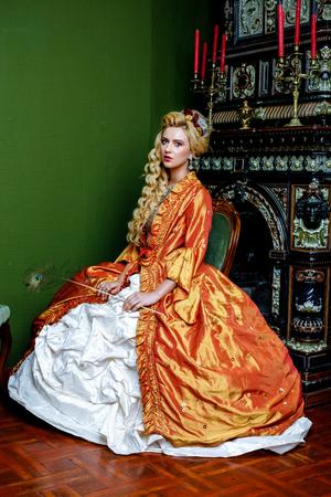 Retro baroque fashion blonde woman wearing gold dress. Stock Photo