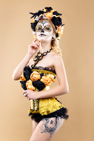 attractive young woman with sugar skull makeup, Dia de los Muertos - Mexican Day of the dead woman wearing sugar skull makeup and flower wreath.