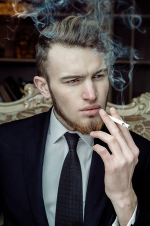 unbutton: Close up portrait picture of a handsome young business man smoking a cigarette
