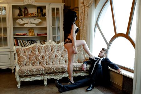 relaciones sexuales: Foto de la manera atractiva romance de la pareja de amantes. Mujer con el pelo rizado negro en ropa interior negro y traje de hombre que lleva