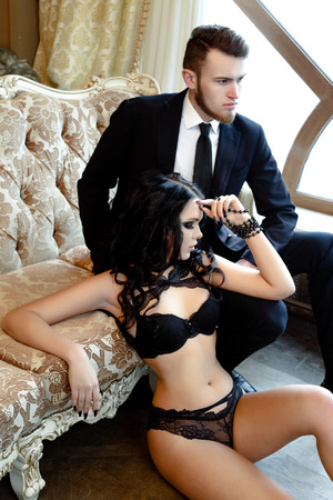 adult intercourse: Fashion photo romance of sexy lovers couple. woman with black curly hair in black underwear and man wearing suit Stock Photo