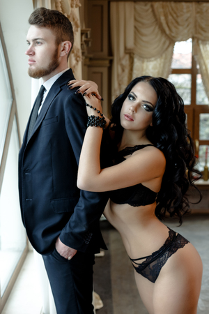 sexual intercourse: Fashion photo romance of sexy lovers couple. woman with black curly hair in black underwear and man wearing suit Stock Photo