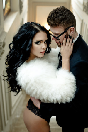 adult intercourse: Fashion photo romance of sexy lovers couple. woman with black curly hair and fur cloth and man wearing suit