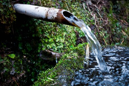 Water flow from bamboo duct into stone basin  Tsukubai  photo