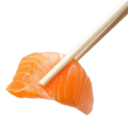 Isolated sliced raw salmon with chopsticks holding it photo