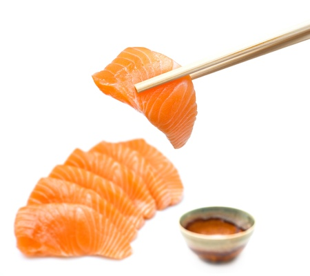 Isolated salmon sashimi set with chopsticks holding a piece of sliced salmon photo