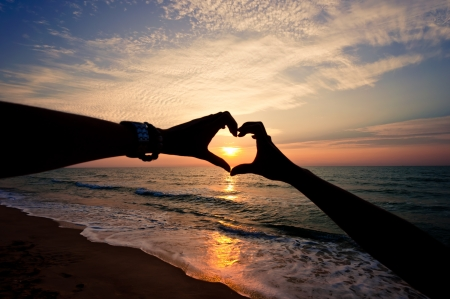 Silhouette hand in heart shape with sunrise in the middle and beach background 版權商用圖片 - 14693909