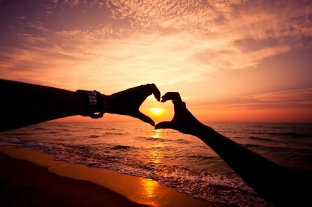 Silhouette hand in heart shape with sunrise in the middle and beach background 版權商用圖片