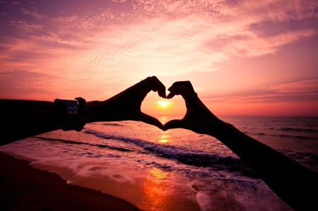 heart shape: Silhouette hand in heart shape with sunrise in the middle and beach background Stock Photo