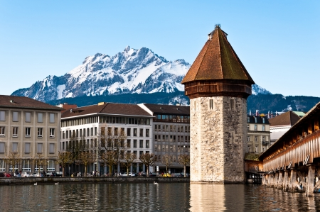 Mount Pilatus with tower and wooden chapel bridge in foreground, Lucerne, Switzerland