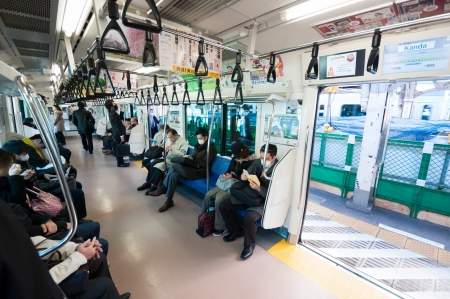Tokyo, Japan - March 27, 2012: JR Chuo line local train of japan, stopped at Kanda station with some passengers in the car.