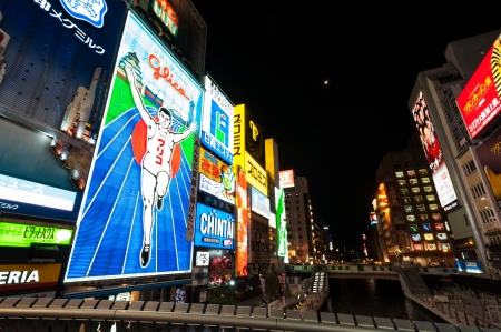 night life: Osaka, Japan - March 30, 2012: The famous running man neon advertisement of glico at Dotonbori shopping street.