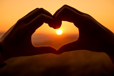 Silhouette hand in heart shape with sunrise in the middle photo