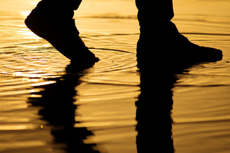Man walking on the water surface with silhouette legs reflection  Stok Fotoğraf