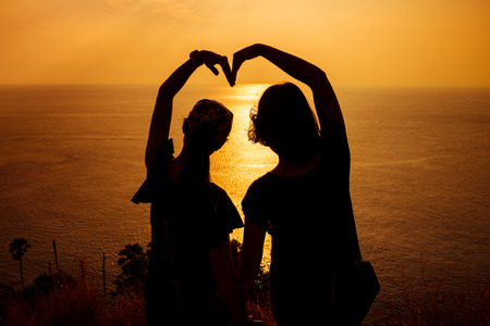 shape silhouette: Silhouette photo of two girls arranged their arms in heart shape with sunset background