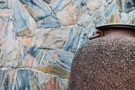 overbuilding: stone wall texture and jar in garden. Stock Photo