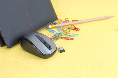 communications tools: Wireless mouse with notebook and paper clip on yellow background