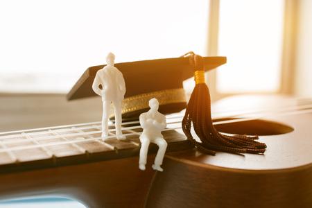 Miniatuur beeldjes Zakenman zittend op ukelele met afstuderen cap. Stockfoto