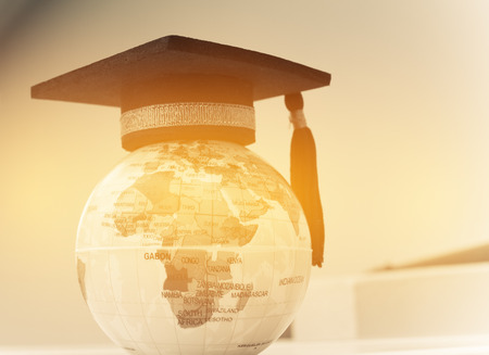 Education in Global, Graduation cap op topmodel Earth. Stockfoto