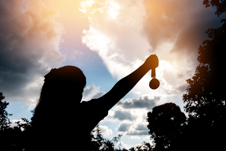 Blurred of silhouette hands raised and holding gold medals with ribbon against sunset background.