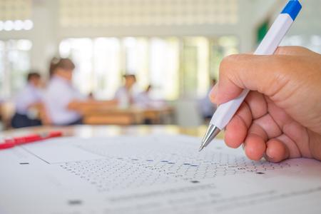 De studenten overhandigen het testen het doen van onderzoek met pentekening geselecteerde keus op antwoordbladen in schoolexamens, de achtergrond van de onduidelijk beeldleerlingenuniversiteit.