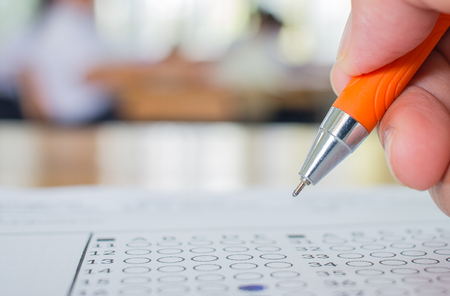 Students hand testing doing examination with pen drawing selected choice on answer sheets in school exams, blur pupils college backgroud. Education system tests concept. Banque d'images