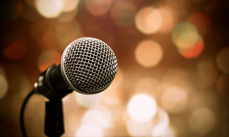 Blurred of microphones in seminar room, talking speech in conference hall light with microphone and keynote.