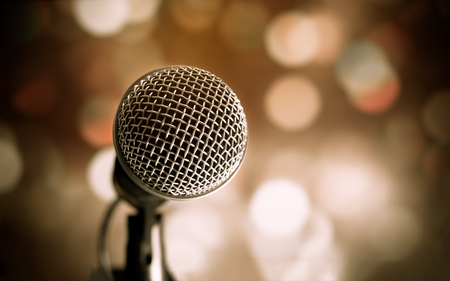 Microphone on abstract blurred of speech in seminar room or speaking conference hall light