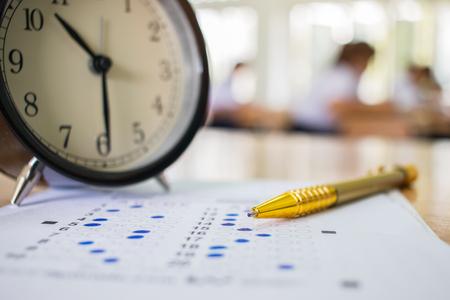 Optische vorm van gestandaardiseerde examens dichtbij wekker met hand die gele pen voor definitief onderzoek houdt Stockfoto
