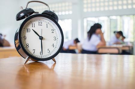 Close-up van Retro wekker met tien uur op lijstleraar in het klaslokaal van onduidelijk beeldstudenten. bestaan.