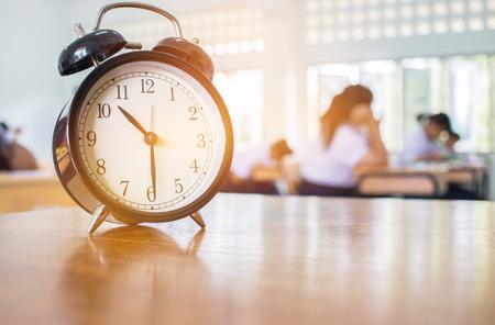 Close-up van Retro wekker met tien uur op lijstleraar in het klaslokaal van onduidelijk beeldstudenten. Stockfoto