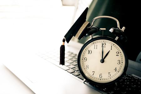 graduation countdown: Graduation cap on top retro alarm clock on computer.