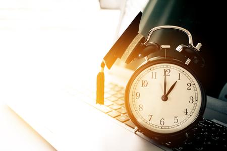 graduation countdown: Graduation cap on top retro Alarm clock on computer. Stock Photo