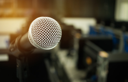 Microphone on abstract blurred of speech in seminar room or speaking conference hall light, computer bokeh background