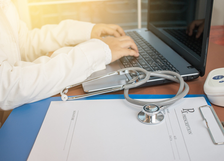 Stethoscope on prescription clipboard and Doctor working an Laptop on desk in hospital, Healthcare and medical concept, selective focus