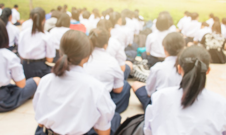 blurred of  group of students in Thailand wear school uniforms sitting in line for school activities in morning, Education Concept methods contemporary educational comprises formal systems in Asia.